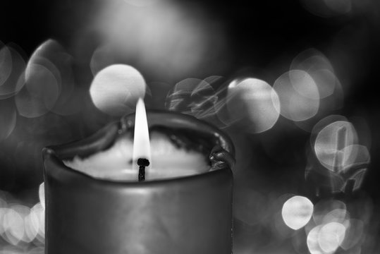 Burning candle against blurred background in black and white colors. Focus on the flame