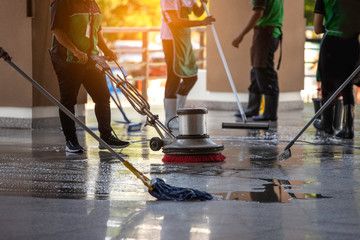 The workers cleaning floor exterior walkway using polishing machine and chemical or acid