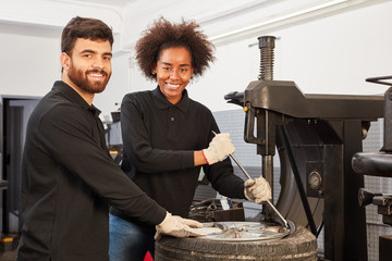 Mechatroniker mit Azubi an der Reifenmontiermaschine