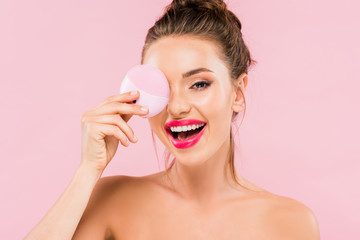 happy naked beautiful woman with pink lips holding facial cleansing brush isolated on pink