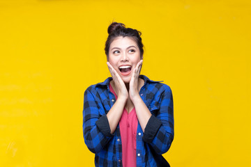 Image of feeling excited, shock, surprise and happy. Young asian woman standing on yellow background. Female face expressions and emotions body language concept.