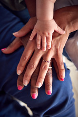Close Up Of Mother With Daughter And Baby Granddaughter From Multi-Generation Family Holding Hands