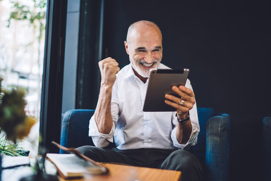 Elderly cheerful man browsing tablet