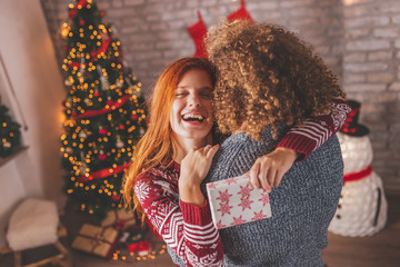 Couple having fun while exchanging Christmas presents