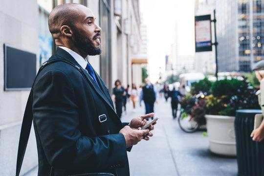 Joyful African American businessman smiling with smartphone in hands