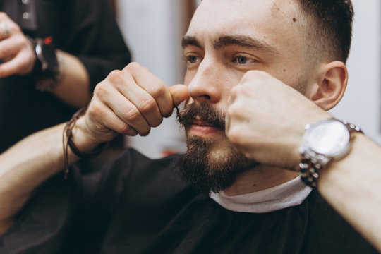 Getting the perfect shape. Close-up side view of a young bearded man getting a beard haircut by hairdresser at barbershop