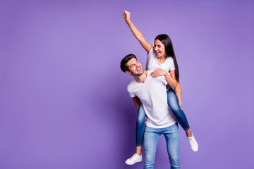 Photo of cheerful positive cute pretty nice couple of two people with her raising fist and him carrying her forward in t-shirt isolated pastel violet color background