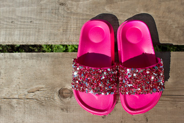 Pink flip flops with shiny rhinestones on an old piece of wood. Place under the text. Summer vacation design concept.