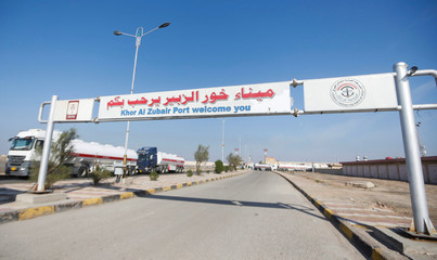 """A sign that reads """" Khor al-Zubair port welcome you '' is seen after demonstrators block the entrance during the ongoing anti-government protests, near Basra"""