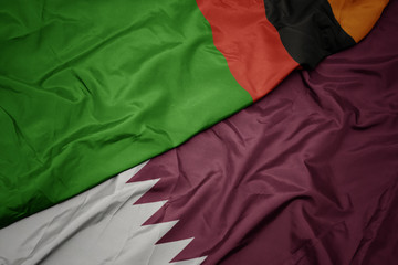 waving colorful flag of qatar and national flag of zambia.