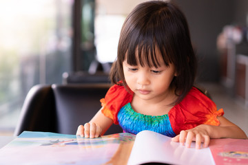 Adorable asian little girl is sitting and reading storybook on the sofa with concentrate happy moment, concept of activity for kid education.