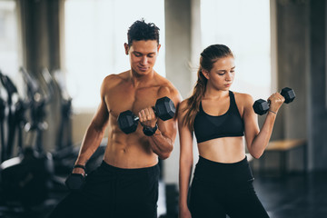 Sporty young couple with dumbbells in functional training fitness gym