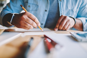 Selective focus on male's hands with electronic smartwatch drawing sketches using yellow pencil and wooden rule indoors.Cropped closeup image of man architect working on startup project using tools