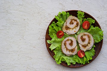Cold appetizer, sliced baked pork roll with fried carrots and onions on fresh lettuce leaves on a clay plate on a bright concrete background. Holiday recipes meat dishes. Top view, copy space.