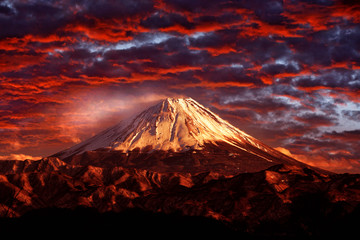 Volcano Fuji during beautiful sunset, red clouds on the sky. Active hill with eruption, twilight in Japan. Mount Fuji,  San, orange evening in Asia landscape. Volcan travelling in Japan.
