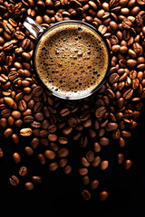 Espresso with coffee foam in a cup on a dark background from coffee beans, top view, selective focus, copy space.