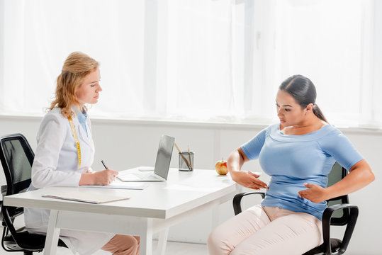 attractive nutritionist sitting at table and listening to patient in clinic