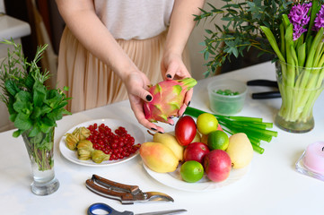 the process of forming a fruit and flower bouquet. tutorial, do it yourself. photo 5, women's hands holding dragon fruit