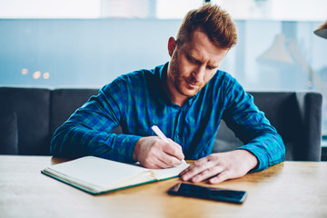 Skilled red haired student writing down homework in copybook studying at wooden table in coworking space.Pensive young man dressed in casual shirt noting checklist in notepad during free time