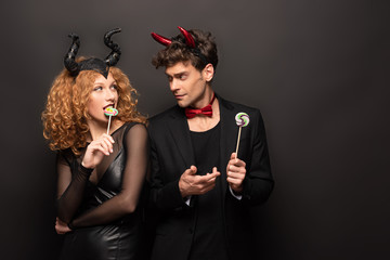 beautiful couple in halloween costumes holding lollipops on black Wall mural
