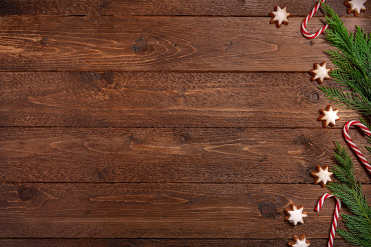 Spruce branches, candy cane, cookies, on dark wooden  background. Christmas, winter concept. Flat lay, top view.