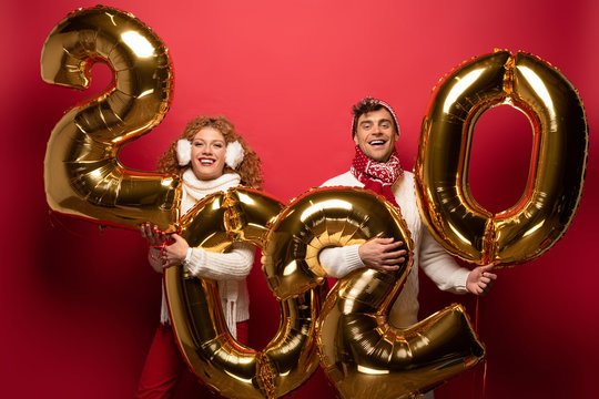 beautiful couple in winter outfit holding new year 2020 golden balloons, on red