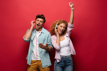 happy couple dancing, singing and listening music with headphones together, isolated on red