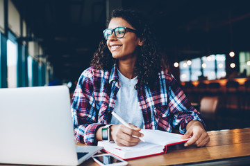 Cheerful african american hipster girl in eyewear writing homework in notepad while looking away studying at laptop.Positive teen with curly hair thinking on plans sitting with notebook at desktop