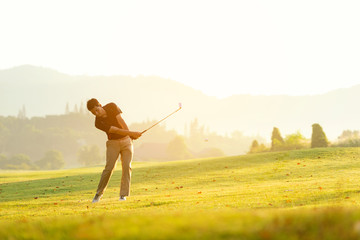 Professional Golfer asian man swing and hitting golf ball practice at golf driving range and fairway in sunny morning day on multiethnic club golf. Lifestyle and Sport Concept