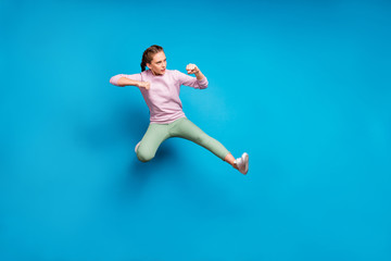 Full length profile side photo of focused sportive girl train her kick boxing skills jump fight enemies wear stylish outfit white sneakers isolated over blue color background