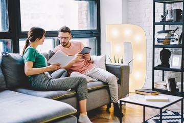 Husband with e-book in hands reading information from literature book in hands of wife resting on couch at home interior.Young marriage with touch pad and bestseller spending leisure time in apartment