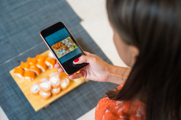 Girl takes pictures of sushi on phone. A girl takes pictures of sushi on the phone that lie on a black wooden table.