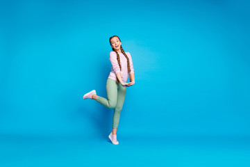 Full length photo of positive cheerful teen girl have free time on walk travel with her friends feel satisfied wear modern outfit pink sneakers isolated over blue color background Wall mural