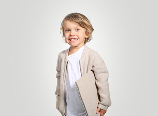 Fotomurales - Very cute little boy with a book in his cardigan