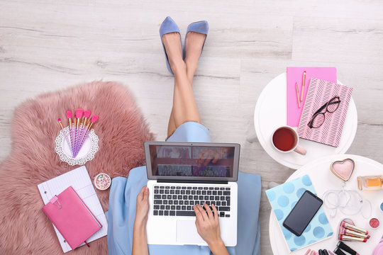 Beauty blogger with laptop and cosmetics sitting on floor, top view