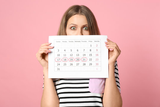 Young woman holding calendar with marked menstrual cycle days on pink background