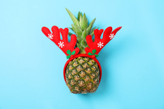 Pineapple with deer horns on blue background, space for text. Juicy fruit