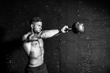 Keuken foto achterwand Fitness Young strong sweaty focused fit muscular man with big muscles holding heavy kettle bell for swing cross training hard core workout in the gym black and white