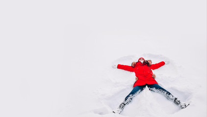 Happy young woman in red lying on snow and making snow angel figure with hands and legs