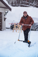 man cleans snow with a shovel