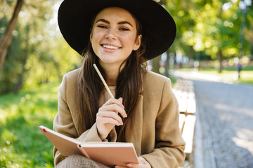 Image of caucasian woman holding diary book while sitting on bench in park