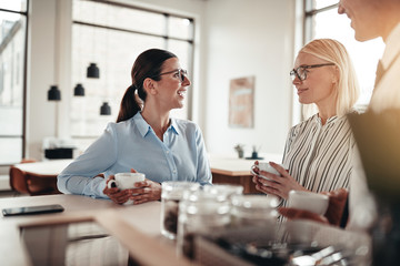 Smiling businesswoman talking with coworkers over coffee in an o