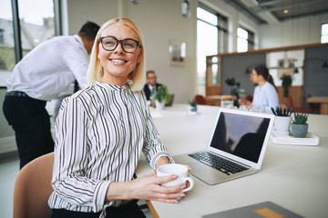 Smiling young businesswoman sitting in an office boardroom drink