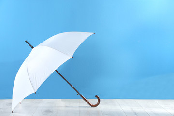Wall Mural - Beautiful white umbrella near blue wall. Space for text