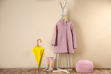 Wall Mural - Yellow umbrella, raincoat and rubber boots near beige wall