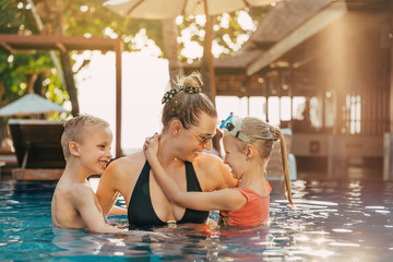 Adorable children playing with their mom in a swimming pool