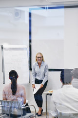 Manager laughing with her staff during an office presentation