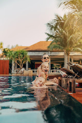 Laughing mother and little children relaxing in a resort pool