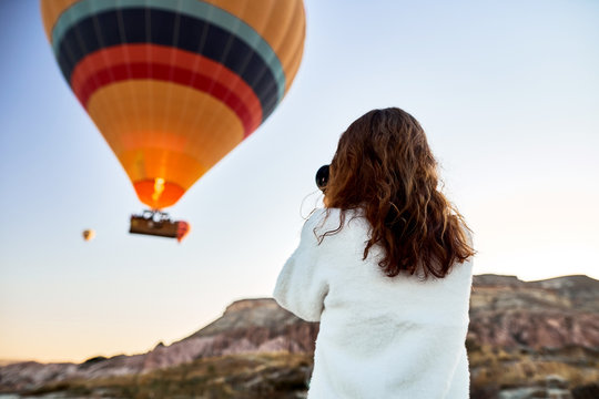 A tourist photographer girl wearing white sweater on a mountain top enjoying wonderful view and taking a picture of balloons in Cappadocia