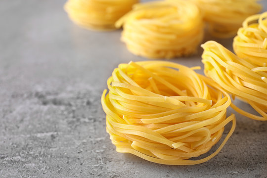 Uncooked angel hair pasta on grey table, closeup. Space for text